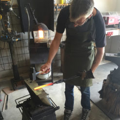 Man hammers glowing knife on anvil